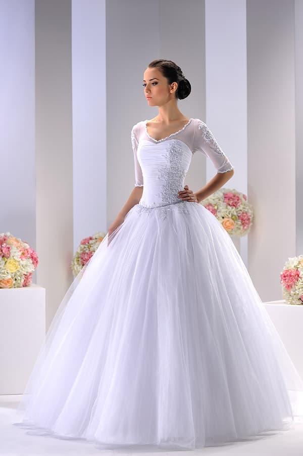 Свадебное платье с полупрозрачной отделкой верха и облегающим рукавом до локтя.