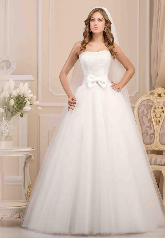 Нежное свадебное платье с деликатным вырезом и атласным бантом на линии талии.
