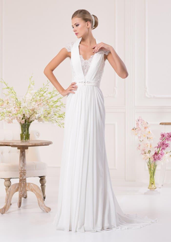 Сдержанное свадебное платье прямого кроя с глубоким декольте, укрытым кружевом, и короткими рукавами.