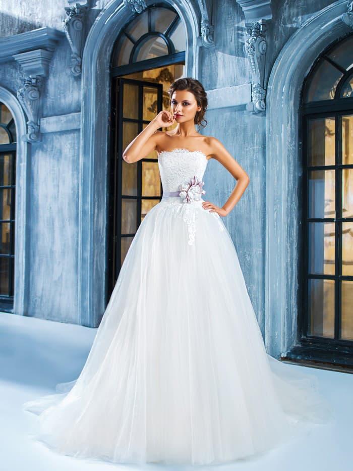 Роскошное свадебное платье с прямой линией декольте и поясом лавандового цвета на талии.
