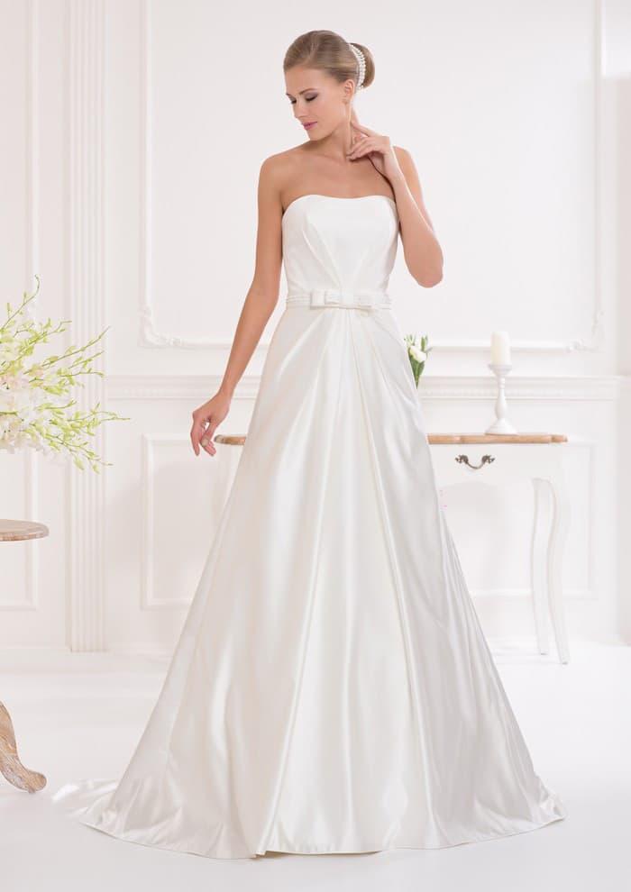 Лаконичное свадебное платье с открытым лифом и изящной юбкой, украшенной складками.