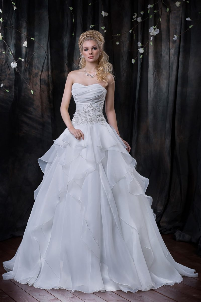 Пышное свадебное платье с фактурными складками по подолу и широким поясом с вышивкой.