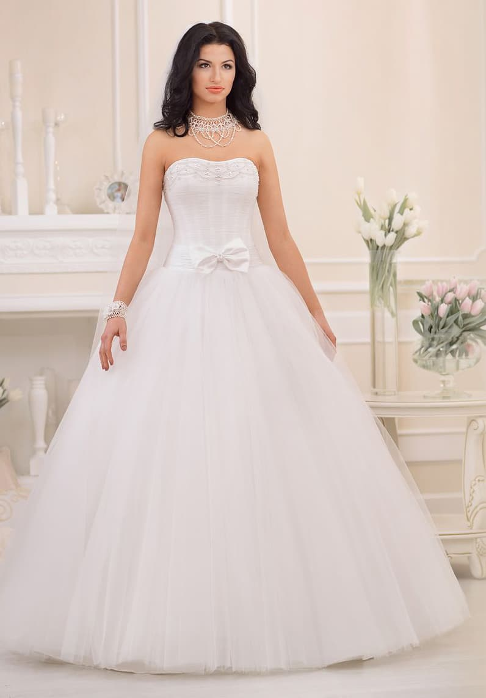Элегантное свадебное платье с деликатным лифом и пышной юбкой, а также бантом на талии.