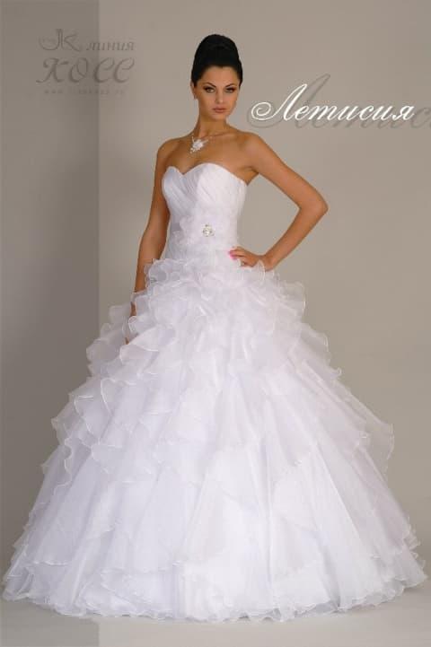Свадебное платье с пышной юбкой, покрытой прозрачными волнами, и открытым верхом.