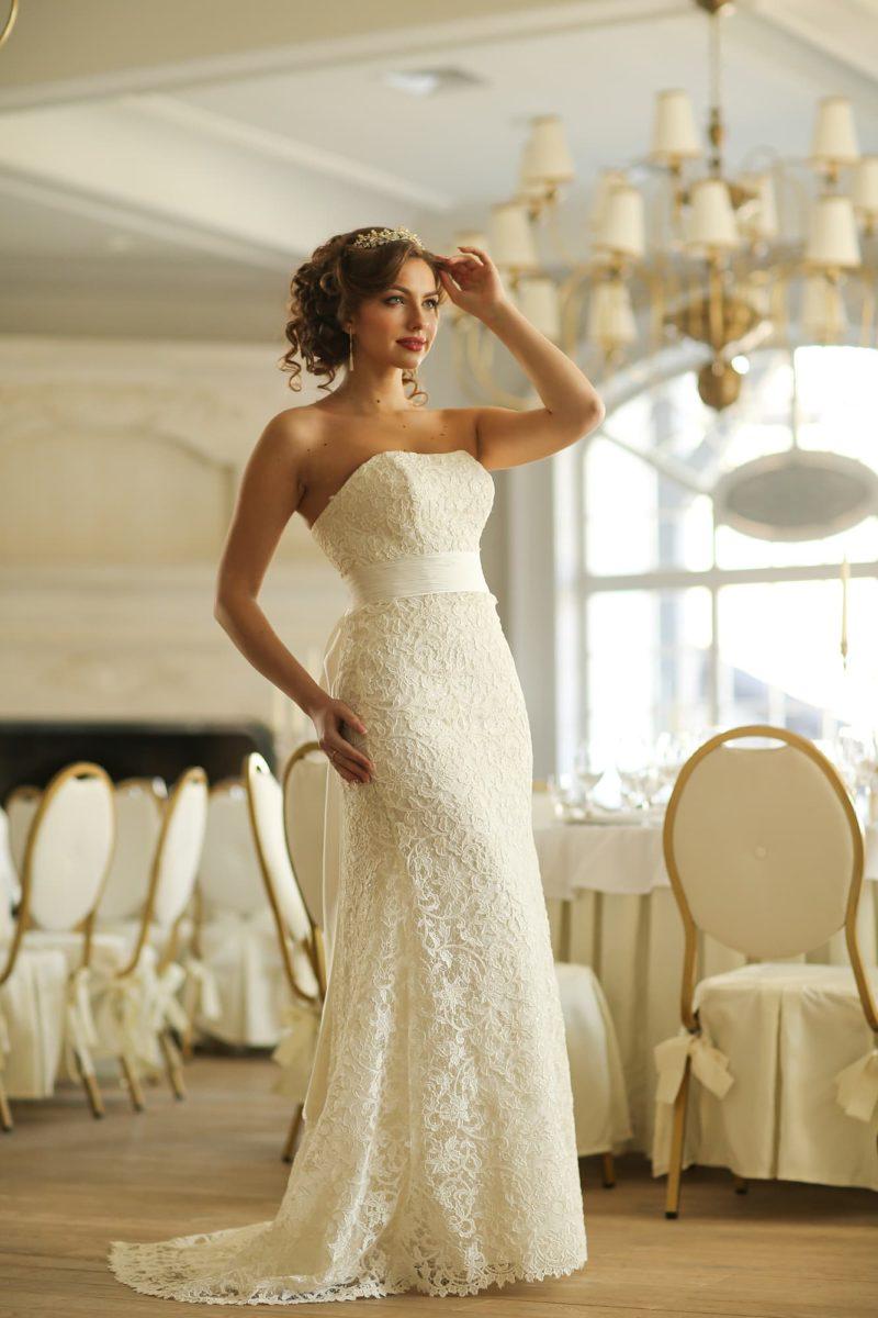 Фактурное свадебное платье прямого кроя со стильным открытым декольте и широким поясом.