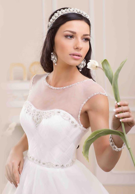 Свадебное платье пышного кроя с тонкой вставкой над лифом и бисерной отделкой верха.