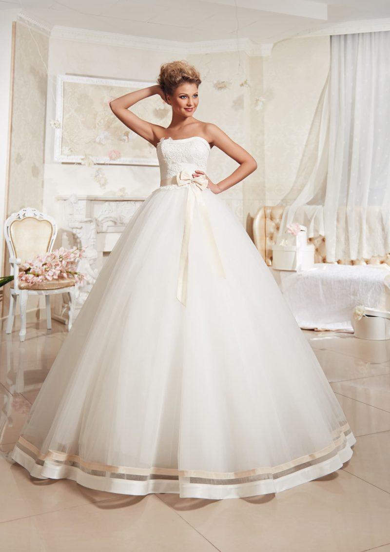 Пышное свадебное платье с открытым лифом и атласной отделкой по нижнему краю подола.