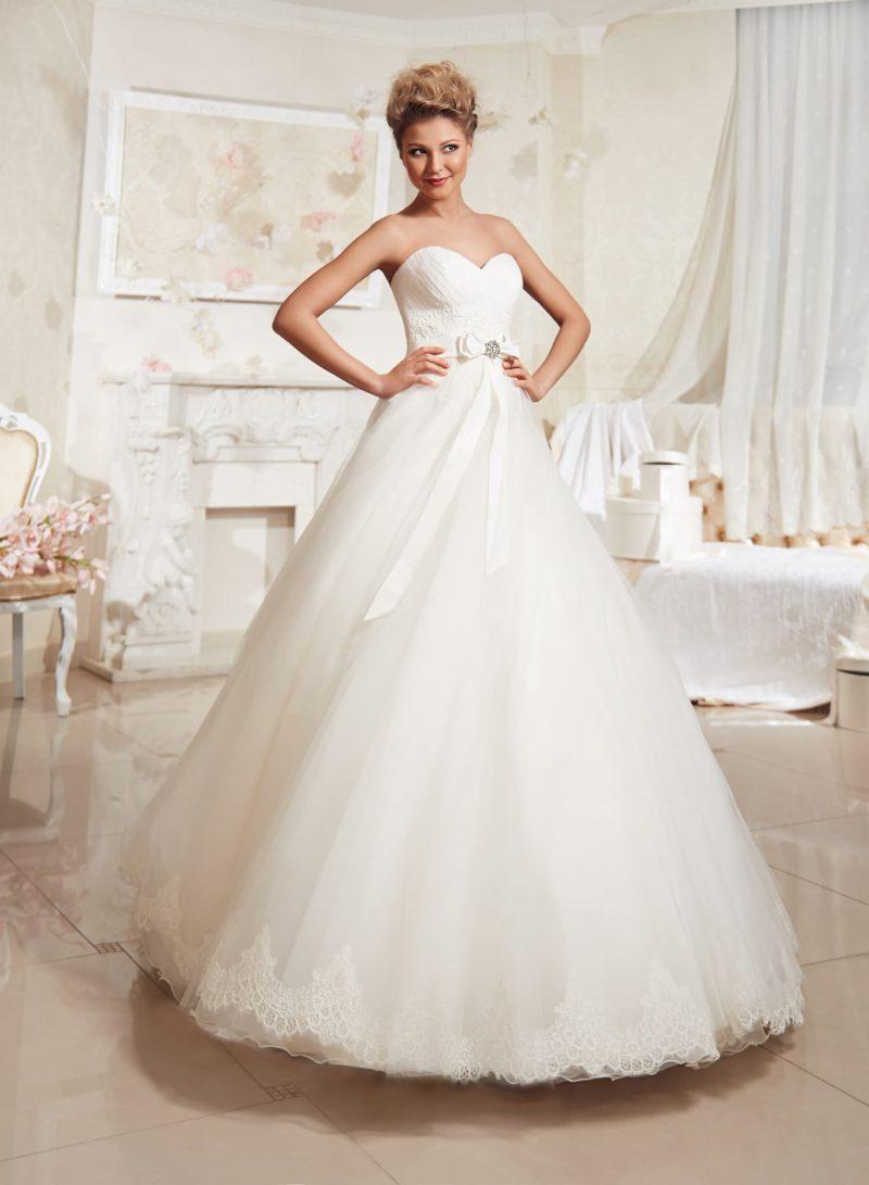 Открытое свадебное платье с лифом в форме сердечка, бантом на талии и кружевом по подолу.