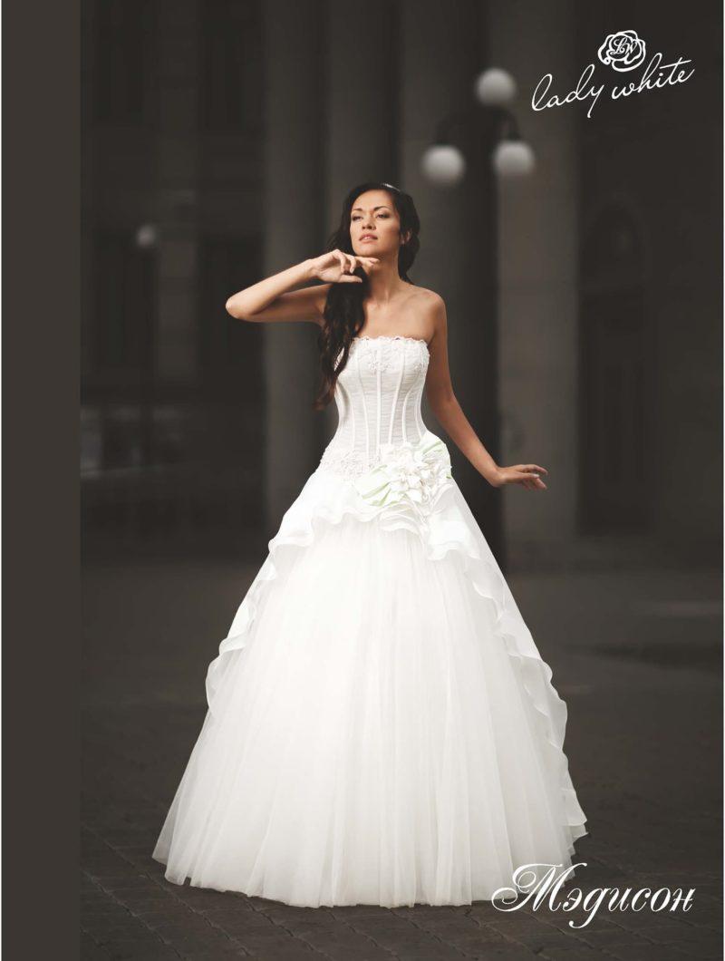 Пышное свадебное платье с открытым лифом и объемным декором юбки.