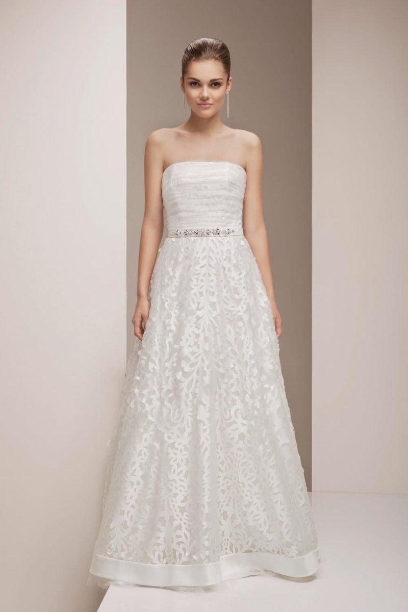 Изысканное свадебное платье с юбкой А-кроя, покрытой эффектным слоем кружева.