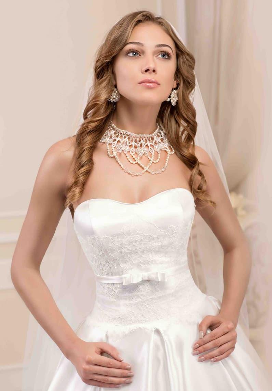 Роскошное свадебное платье с волнами по подолу и открытым корсетом, украшенным по линии талии.