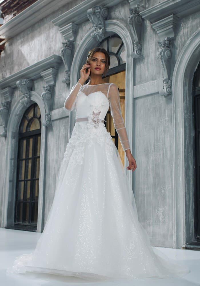 Закрытое свадебное платье «принцесса» с объемной отделкой подола и длинными прозрачными рукавами.