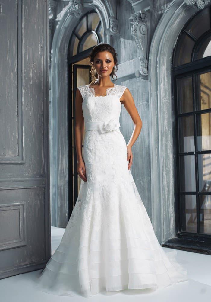 Свадебное платье с широкими кружевными бретелями, поясом на талии и облегающим кроем.