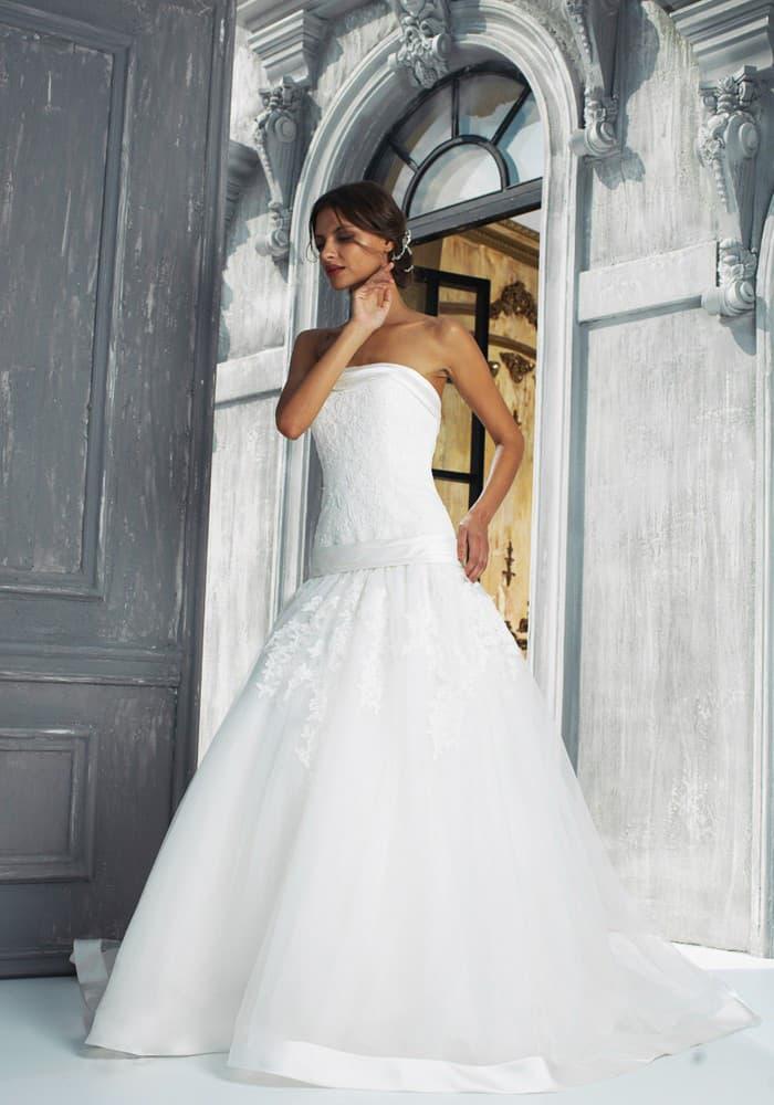 Свадебное платье с заниженной линией талии, прямым лифом и многослойной юбкой.
