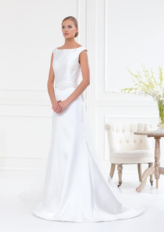 Атласное свадебное платье с вырезом лодочка и широкими бретелями на плечах.