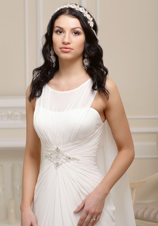 Элегантное свадебное платье с отделкой из мелких драпировок и полупрозрачной ткани.