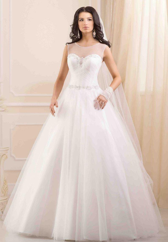 Сдержанное свадебное платье с закрытым лифом, драпировками на корсете и пышным низом.
