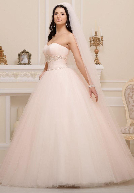 Кремовое свадебное платье с открытым лифом в форме сердца и многослойным подолом.