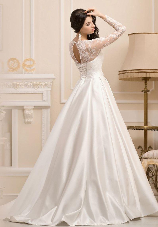 Сияющее свадебное платье с пышной юбкой из атласной ткани и длинными кружевными рукавами.