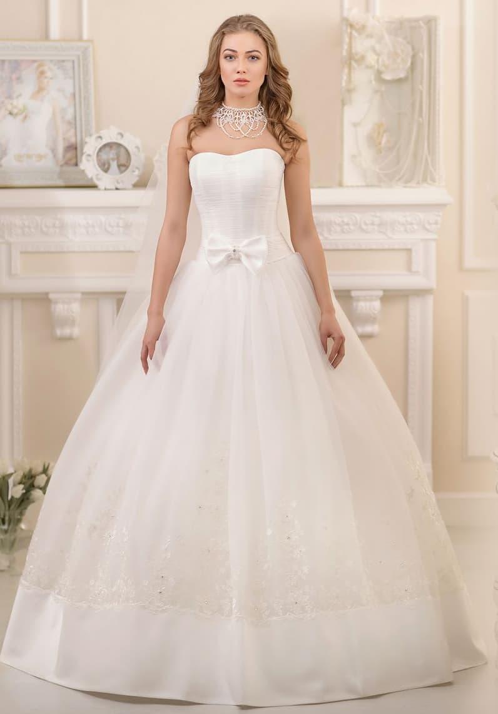 Изысканное свадебное платье с лаконичным открытым корсетом, украшенным атласным бантом.