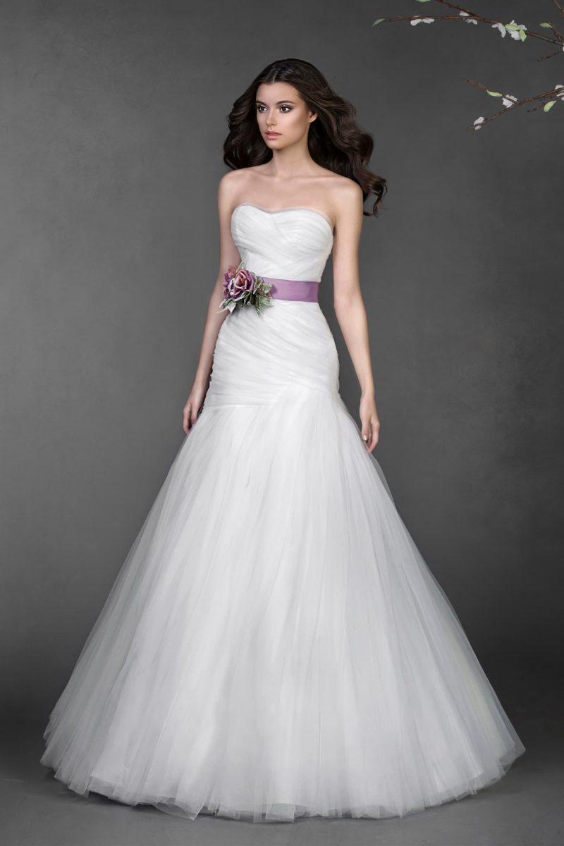 Лаконичное свадебное платье облегающего кроя, дополненное драпировками и цветным поясом.