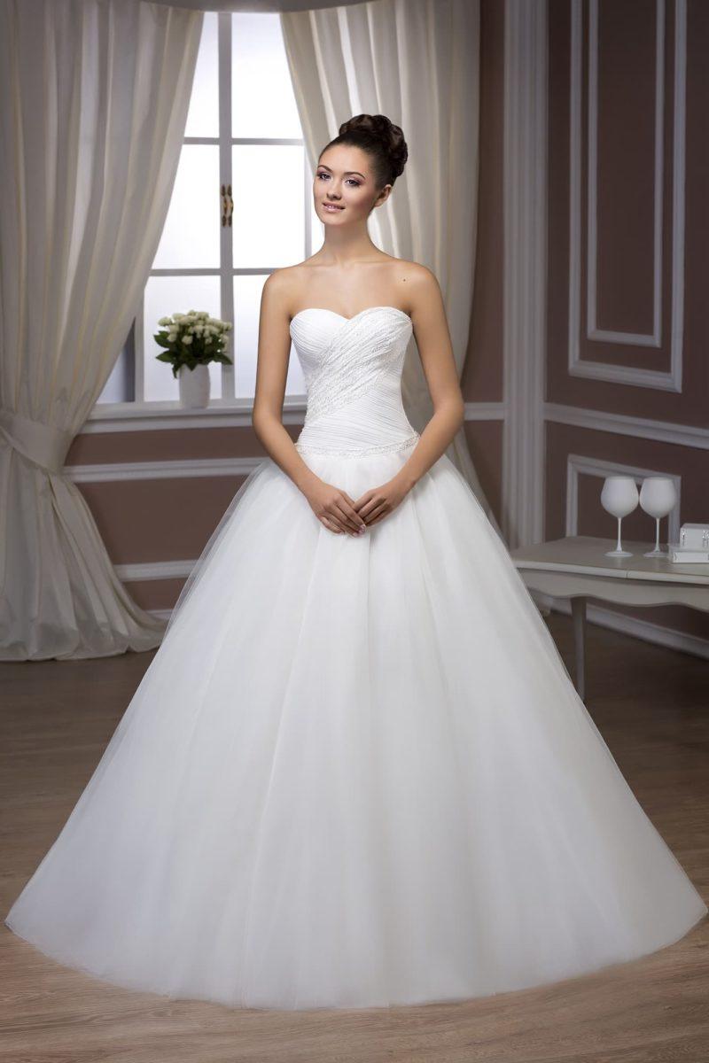 Пышное свадебное платье с лифом в форме сердца и лаконичным декором драпировками.