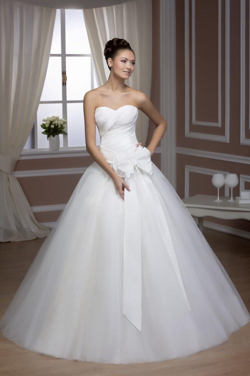 Пышное свадебное платье с лаконичным низом и корсетом, украшенным крупным бантом.