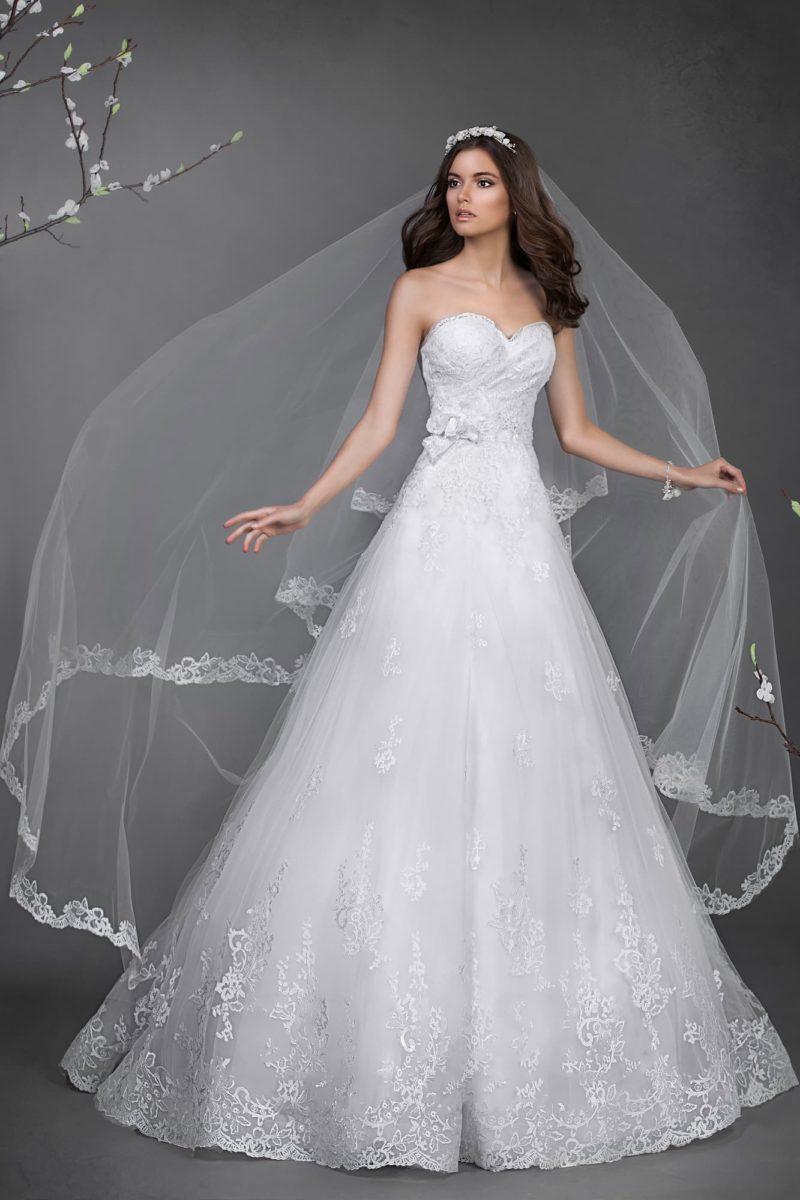 Пышное свадебное платье с женственным вырезом декольте и кружевной отделкой юбки.