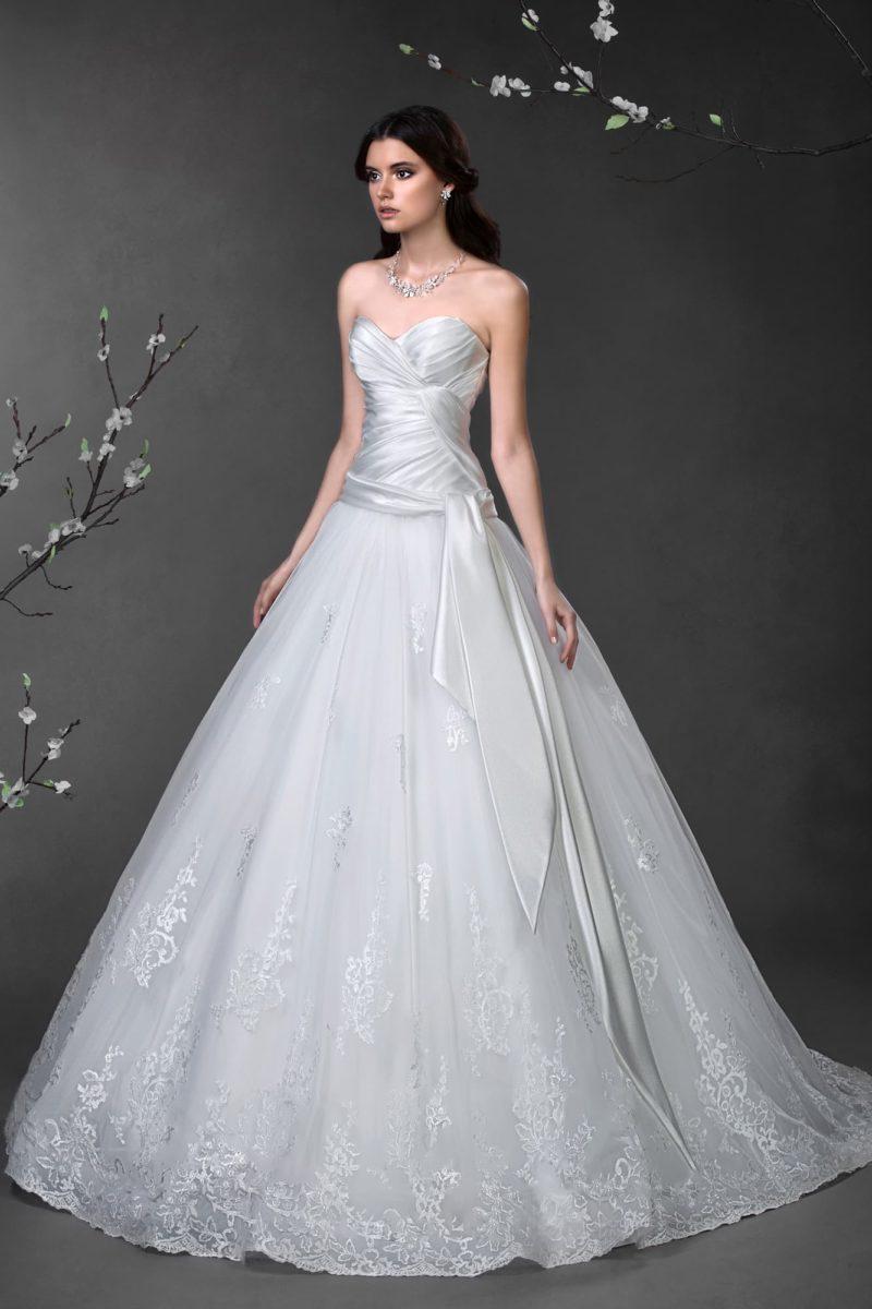 Свадебное платье с объемным кружевным подолом и атласным лифом с драпировками.