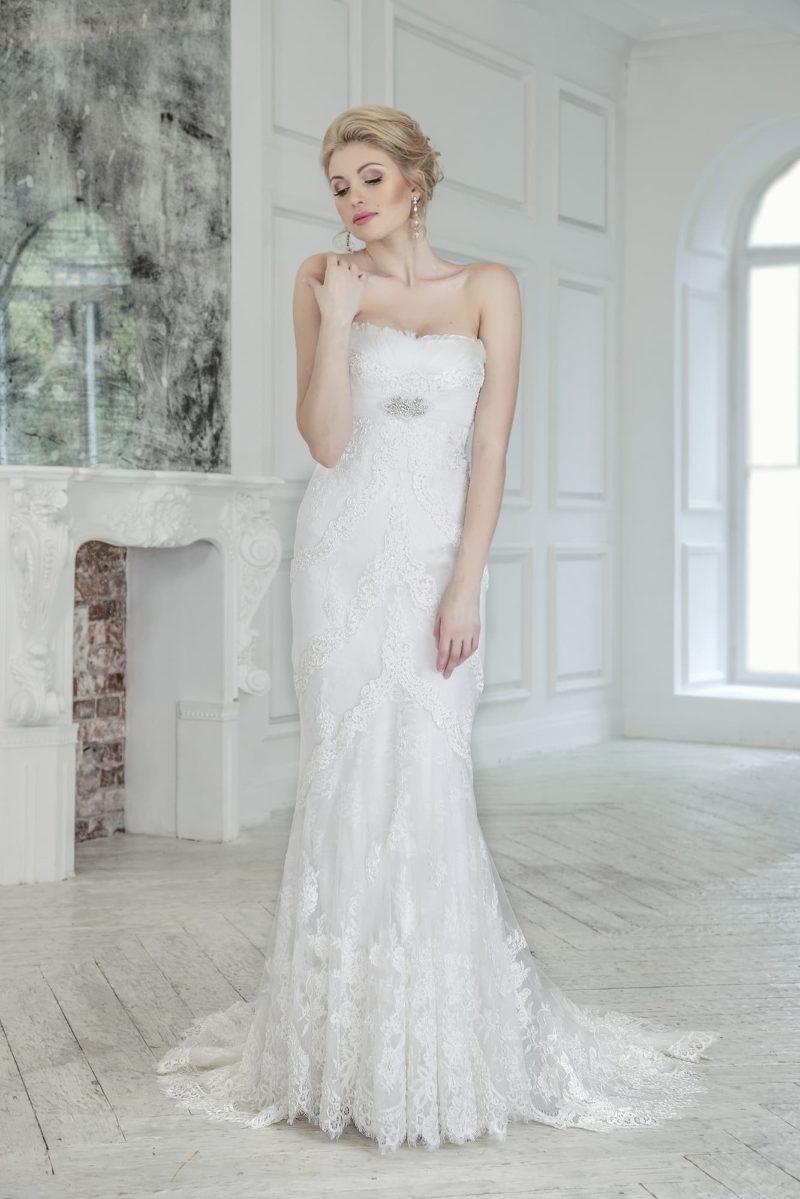 Свадебное платье с открытым лифом прямого кроя и кружевным шлейфом.