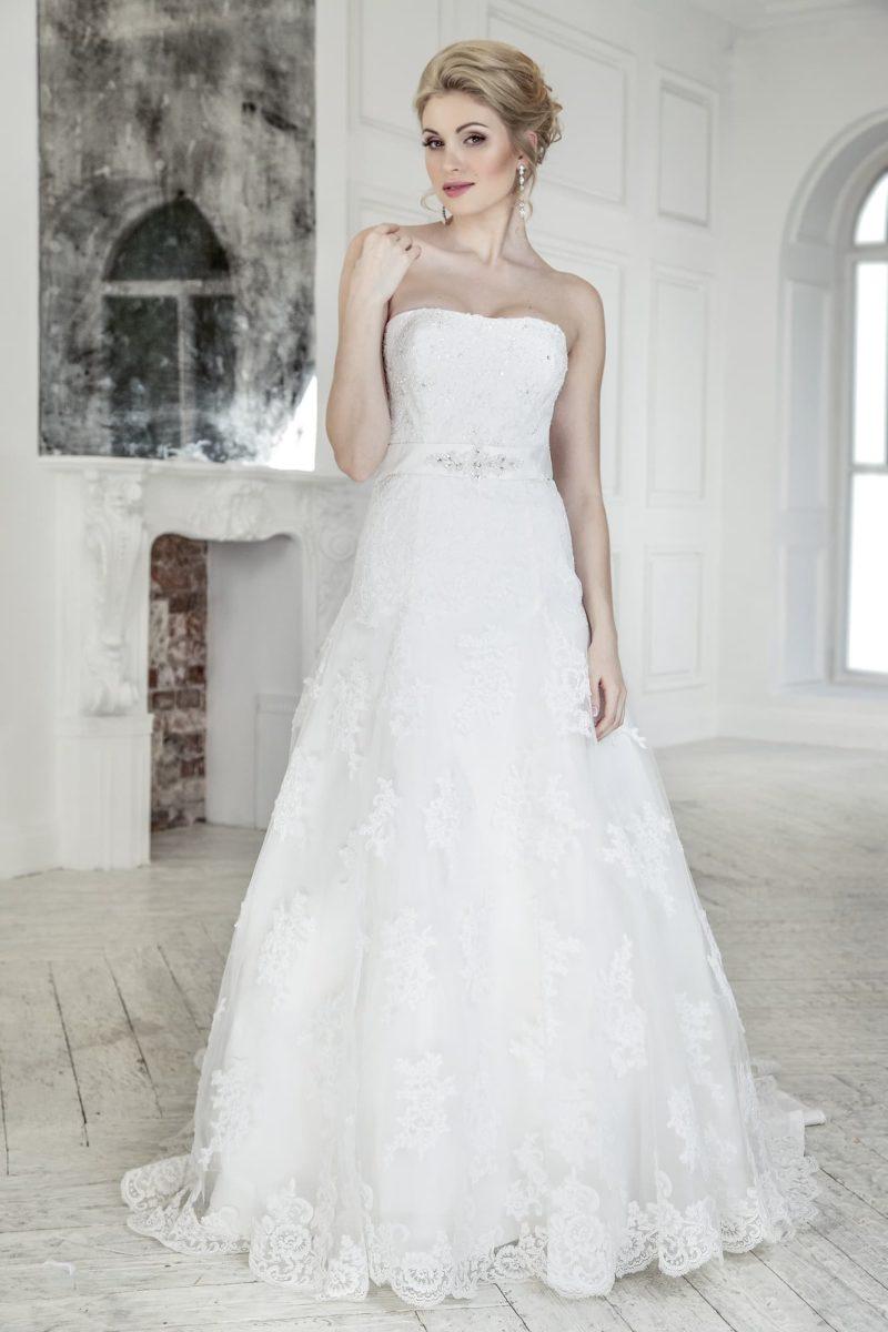 Свадебное платье «трапеция» с открытым лифом прямого кроя и блестящей вышивкой.