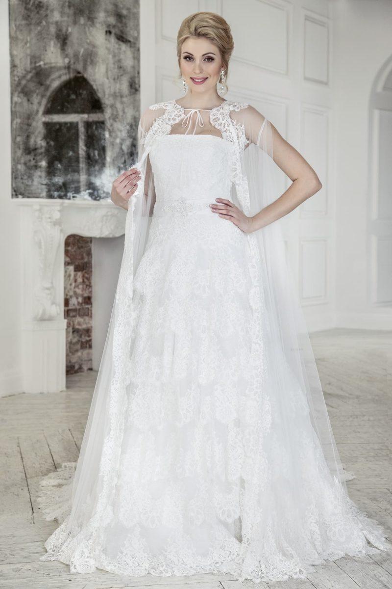 Свадебное платье «принцесса» с многоуровневой юбкой и прозрачной накидкой на плечах.
