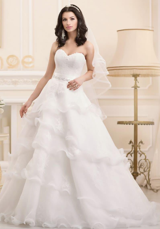 Открытое свадебное платье с полупрозрачными оборками по всей длине пышного подола.
