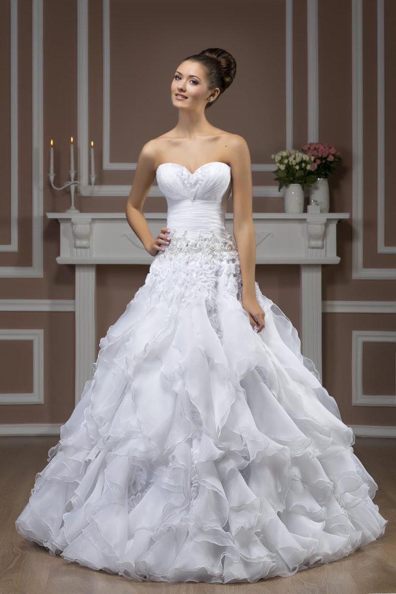 Пышное свадебное платье с романтичной отделкой подола и открытым лифом с глубоким декольте.