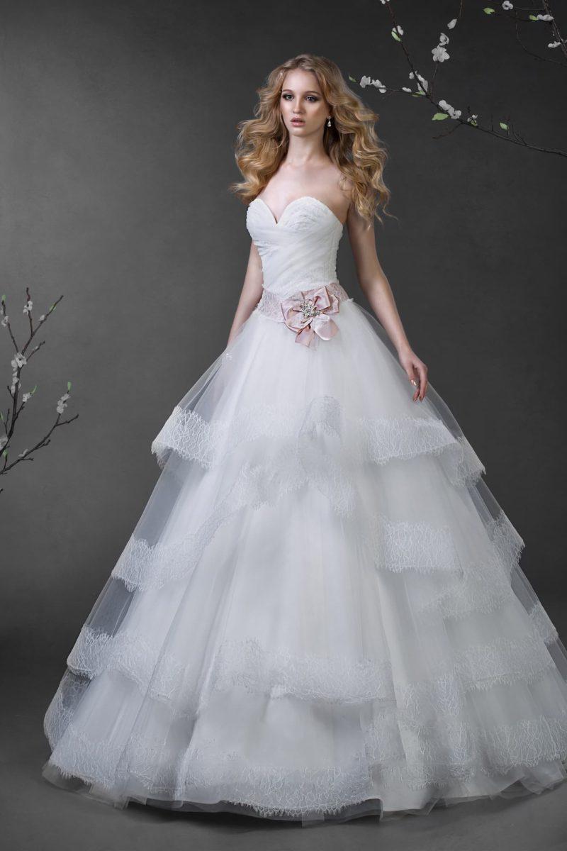 Свадебное платье с глубоким декольте в форме сердца и многоярусной пышной юбкой с кружевом.