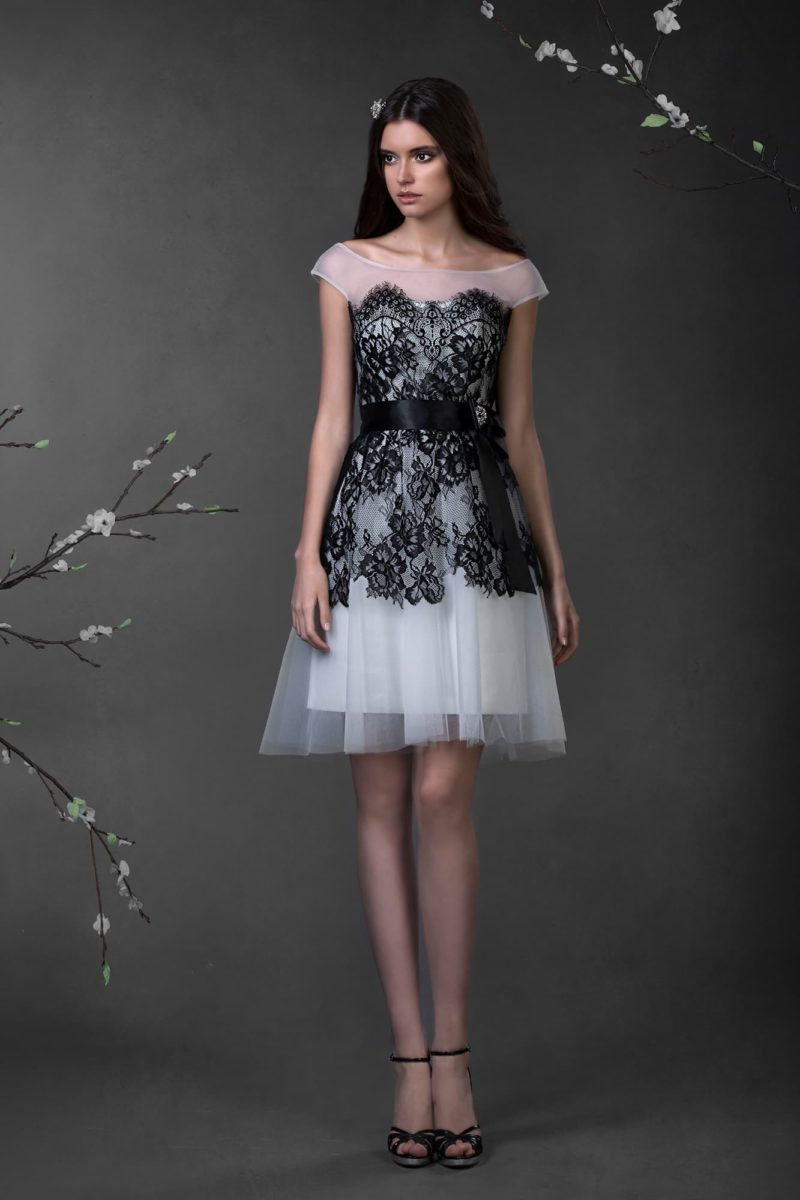 Короткое свадебное платье, отделанное черным кружевом по корсету и юбке, с широким округлым вырезом.