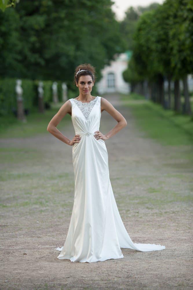 Прямое свадебное платье с драматичным вырезом, украшенным кружевной вставкой.