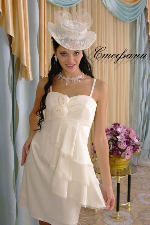 Короткое свадебное платье с асимметричными оборками по корсету и узкими бретелями.