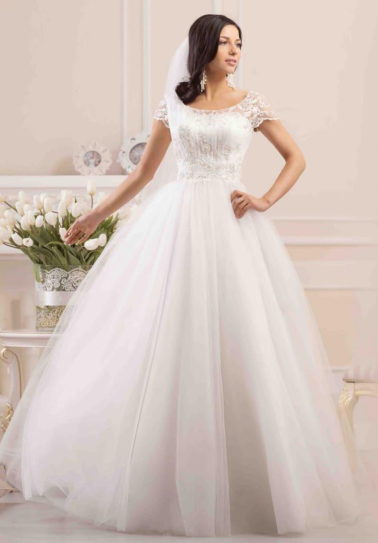 Очаровательное свадебное платье с объемной многослойной юбкой и закрытым верхом с коротким рукавом.