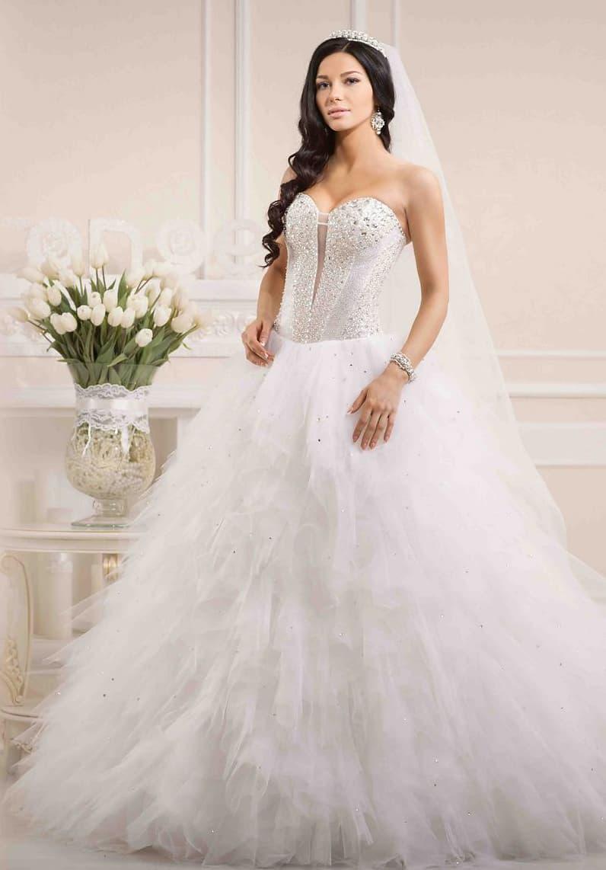 Кокетливое свадебное платье с оборками по подолу и глубоким вырезом на открытом корсете.