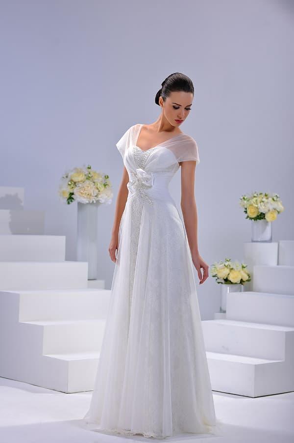 Прямое свадебное платье с широкими полупрозрачными бретелями и высокой талией.