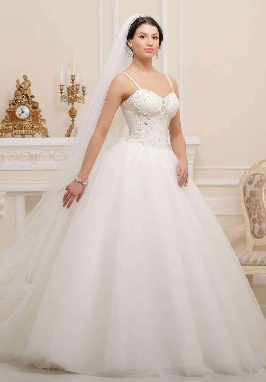 Классическое свадебное платье с объемным подолом и стильным корсетом с узкими бретелями.