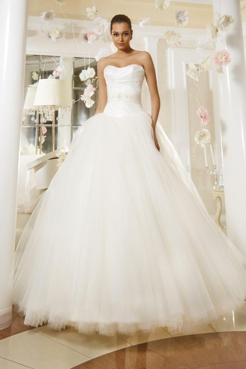 Пышное свадебное платье с женственным открытым корсетом и лаконичным атласным поясом на талии.