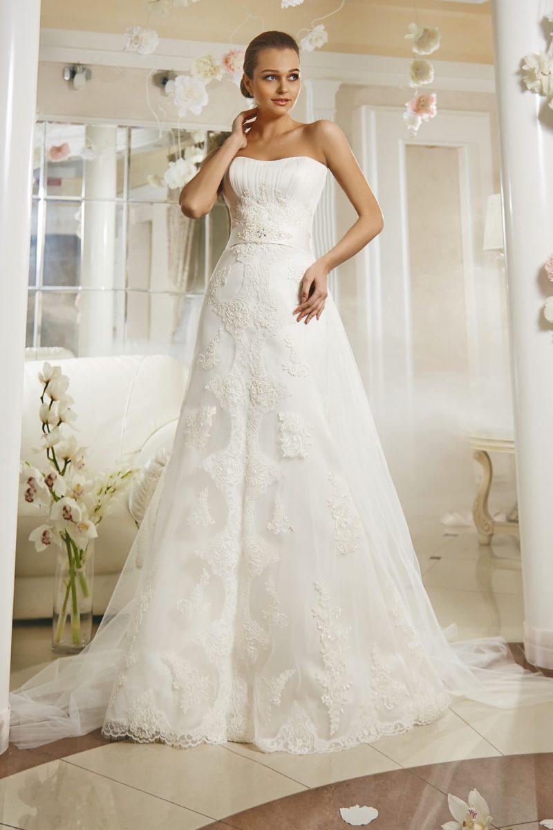 Открытое свадебное платье с драпировками на корсете и кружевным декором многослойной юбки.