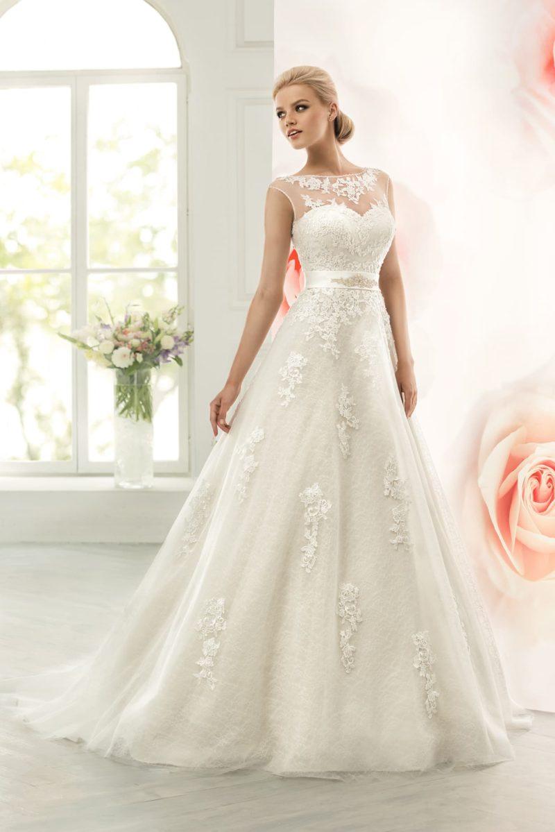 Элегантное свадебное платье кроя «трапеция» с лифом, закрытым полупрозрачной тканью.