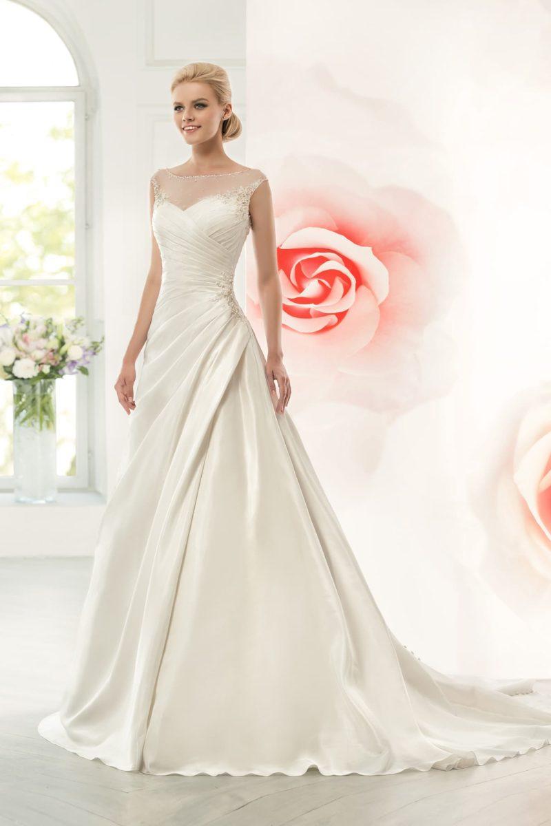 Свадебное платье с роскошными драпировками атласа по подолу и полупрозрачным декором спинки.