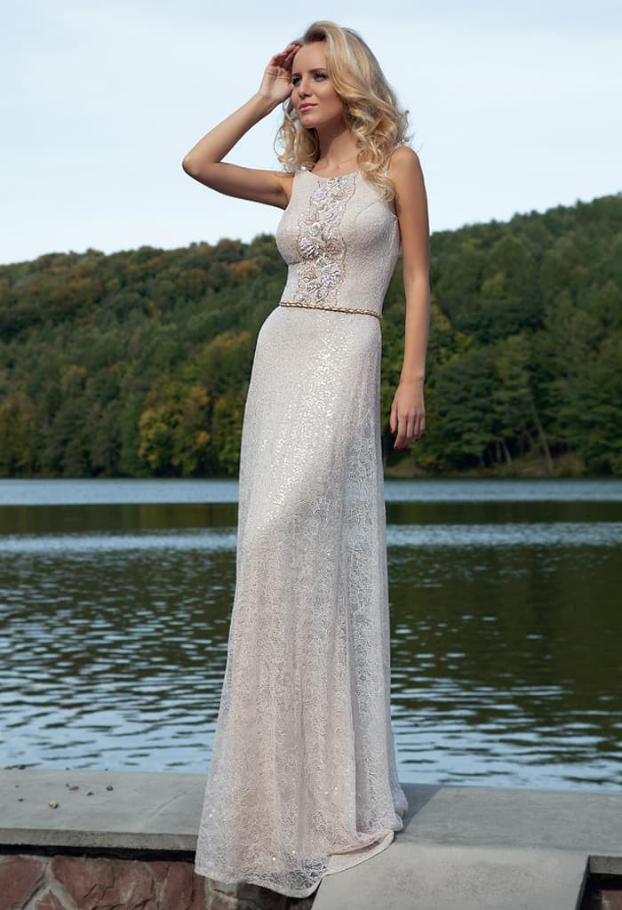 Вечернее платье из глянцевой серебристой ткани с округлым вырезом и блестящим поясом.