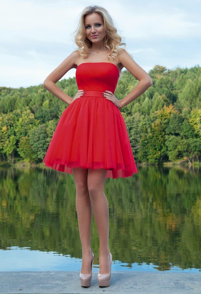 Стильное вечернее платье красного цвета с открытым лифом и юбкой до середины бедра.