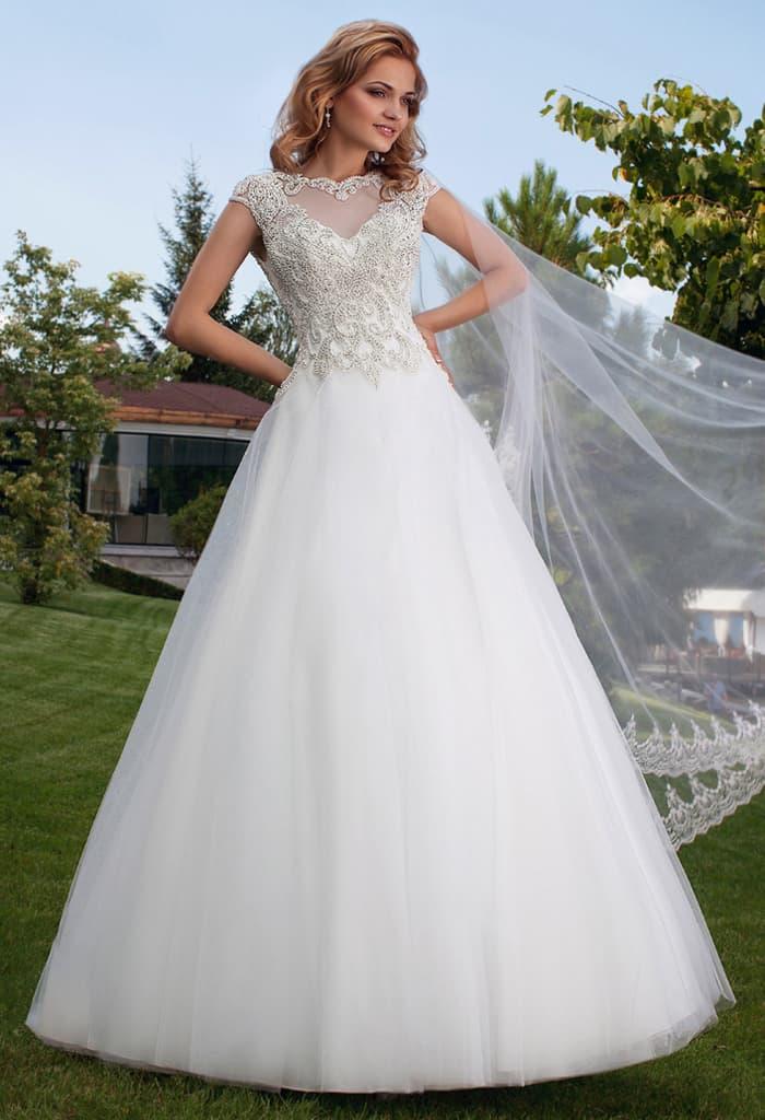 Пышное свадебное платье с полупрозрачной вставкой на спинке и короткими рукавами.