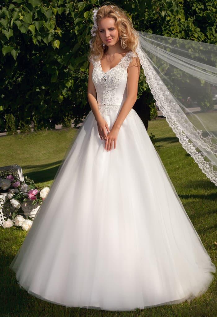 Роскошное свадебное платье с многослойным низом и кружевным декором V-образного лифа.